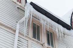 I grandi ghiaccioli appendono sulla facciata della casa di legno Fotografia Stock