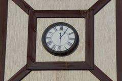 I grandi orologi rotondi appendono su una parete di costruzione marrone grigia fotografia stock libera da diritti