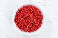 I granelli di pepe rossi pepano il granello di pepe da sopra il bordo di legno della ciotola Fotografia Stock