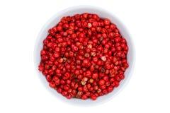 I granelli di pepe rossi pepano il granello di pepe da sopra la ciotola isolata su wh Immagine Stock