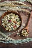 I grani del grano intero e dell'avena si sfaldano in ciotola di legno Fotografie Stock