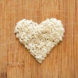 I grani del riso bianco nel cuore modellano sul tagliere di legno, nel formato quadrato per i media, le insegne e gli ambiti di p Immagini Stock