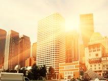 I grattacieli in colpo del centro davanti al sole con i sunflares, colore caldo hanno tonificato il colpo Fotografie Stock