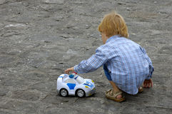When I grow up I wanna be ... A small child, playing with a toy police car, against a plain background of paving stones. Space for text on the stones Stock Image