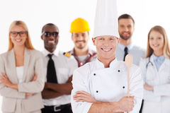When I grow up I will be a chef. Confident male chef in uniform keeping arms crossed and smiling while group of people in different professions standing in the Stock Photos