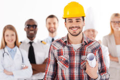 When I grow up I will be an engineer. Confident young men in hardhat holding blueprint and smiling while group of people in different professions standing in Stock Image