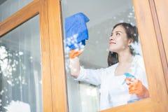 I guanti arancio di usura femminile asiatica sta pulendo la sua casa fotografie stock libere da diritti
