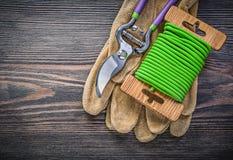 I guanti della sicurezza dei tagli della potatura fanno il giardinaggio cavo del legame sul bordo di legno garde Fotografia Stock Libera da Diritti