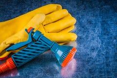 I guanti di giardinaggio di cuoio gialli innaffiano il concep dell'agricoltura dello spruzzatore Fotografie Stock