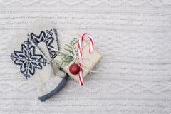 I guanti ed il regalo di natale con il bastoncino di zucchero su bianco hanno tricottato il fondo Fotografia Stock