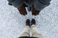 I guanti marroni delle donne e gli stivali casuali degli uomini che stanno sull'asfalto hanno riguardato la superficie granulosa  Fotografie Stock