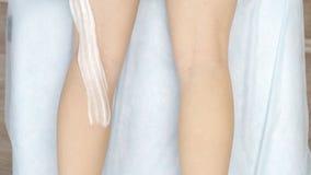 I guanti neri shugaring matrici deftly hanno applicato la pasta sui piedi della ragazza, quindi sulle rotture taglienti dei movim stock footage