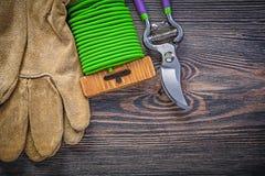 I guanti protettivi di cuoio delle cesoie fanno il giardinaggio cavo del legame sulla BO di legno Fotografia Stock Libera da Diritti