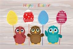 I gufi tengono le uova decorate Pasqua su un bastone multicolored Vettore illustrazione vettoriale