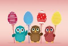 I gufi tengono le uova decorate Pasqua su un bastone multicolored Vettore illustrazione di stock