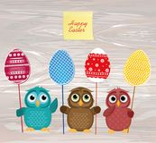 I gufi tengono le uova decorate Pasqua su un bastone multicolored vuoto illustrazione vettoriale