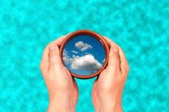 I händerna av en kopp med en reflexion av moln på bakgrunden av vatten royaltyfri fotografi