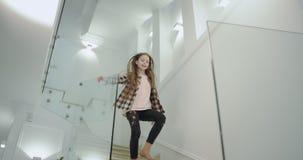 I härliga moderna flicka för ett hus mycket lysande lyckliga nio år med ett långt lockigt hår som ner kör till trappan till stock video