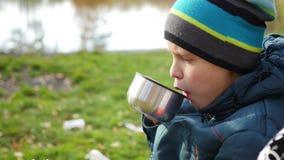 I höst parkera grabbsammanträde på gräsmattan och dricka varmt te, går i den nya luften closeup stock video