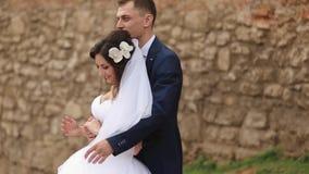I halvfigur skott av den lyckliga unga stilfulla nygift personpardansen i den soliga gatan arkivfilmer