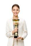 I halvfigur stående av affärskvinnan med den guld- koppen royaltyfri foto