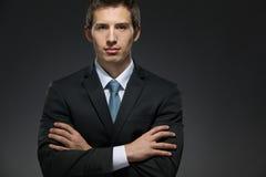I halvfigur stående av affärsmannen med korsade armar fotografering för bildbyråer