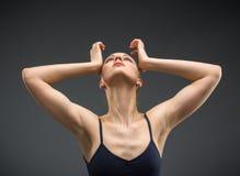 I halvfigur stående av dansballerina med händer på huvudet royaltyfri foto