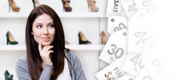 I halvfigur stående av den unga kvinnan som söker efter stilfulla skor royaltyfri foto