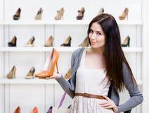 I halvfigur stående av kvinnan som håller skon arkivbild