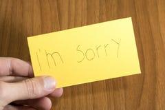 I handwrite spiacente del ` m. su una carta gialla con una penna su una tavola fotografia stock libera da diritti