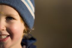 I Am Happy. Close up of a young blonde boy wearing a woolly hat and smiling royalty free stock image