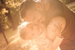 I am happy when I with daddy. Smiling father and his little girl plying in park together. Close up stock photos