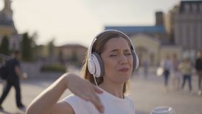 I am happy and free! funny girl walking in the city, early morning. woman in big headphones dancing and singing 4K