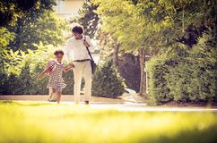 I am happy for the school. African American father and his daughter walking trough park royalty free stock image