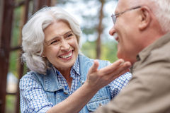 I am happy with you. I still love you. Joyful old women is touching male face and looking at her husband with gentleness. They are sitting and smiling Royalty Free Stock Image
