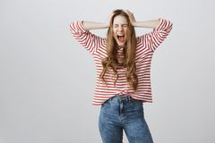 I hate adults. Portrait of depressed and angry european teenage girl screaming with closed eyes and holding hands on Royalty Free Stock Photos