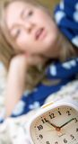 I hate alarm clocks. Sleepy woman shuts off alarm clock stock photo