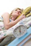 I hate alarm clocks. Sleepy woman shuts off  alarm clock Stock Images