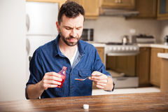 I hate drinking cough syrup. Portrait of a man looking disgusted while holding a spoonful of cough syrup at home Royalty Free Stock Photography