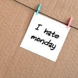 I hate monday. Note is written on a white sticker that hangs wit. H a clothespin on a rope on a background of brown cardboard stock photos