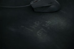 I hate my job, written on used mouse pad and a mouse in the background Royalty Free Stock Images