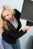 I hate technology. Beautiful lady throwing a laptop on the floor Stock Photography