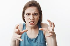 I hate you. Close up portrait of negative handsome european young woman with dark hair in blue shirt looking with mad. Expression, going to grab boyfriends neck Stock Photo