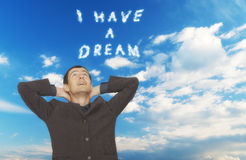 I have a dream. Handsome young businessman looking up in the sky where clouds spell out I HAVE A DREAM royalty free stock photography