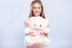 I have a gift for you!. Attractive young woman with teddy bear while standing over gray background Royalty Free Stock Images