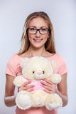 I have a gift for you!. Attractive young woman with teddy bear while standing over gray background Royalty Free Stock Image