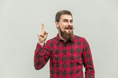 I have idea! Handsome businessman with beard and handlebar mustache looking at camera with finger up. Studio shot, on gray background royalty free stock images