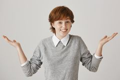 I have no clue. Portrait of carefree cute redhead female model with freckles shrugging and standing with spread hands stock image
