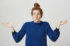 I have no idea, it was not my fault. Portrait of confused and troubled cute redhead woman in winter sweater shrugging. With spread palms, looking aside, trying Royalty Free Stock Photography