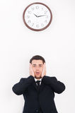 I have no time!. Shocked young man in formalwear looking at camera and holding head in hands while standing under the wall clock Royalty Free Stock Photo